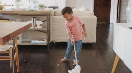 mopping : Three year old African American boy cleaning dining room floor with a mop, full length