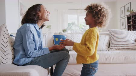 díszített : Pre-teen African American girl giving her mum a homemade painted plant pot as a gift, side view