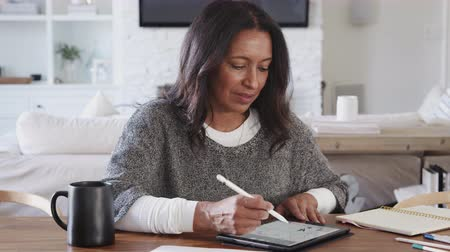 focus on foreground : Middle aged woman sitting at a table using a tablet computer and stylus, front view, zoom out Stock Footage