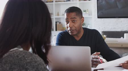 dokumentum : Middle aged African American man with laptop computer giving financial advice to a woman at her home, close up Stock mozgókép