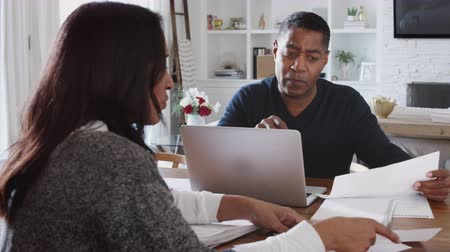 each other : African American male financial advisor discussing documents with a woman at her home, close up