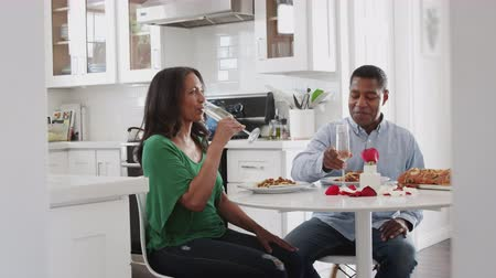 beso : Middle aged African American couple making a toast before eating a romantic meal in their kitchen