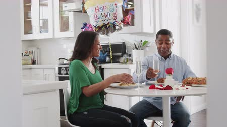 pocałunek : Middle aged African American couple making a toast before eating a birthday meal in their kitchen