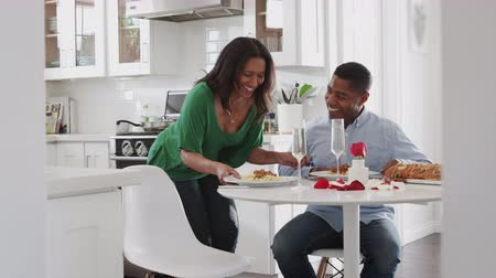 pocałunek : Middle aged African American man sitting in the kitchen while his partner serves a romantic meal for them Wideo