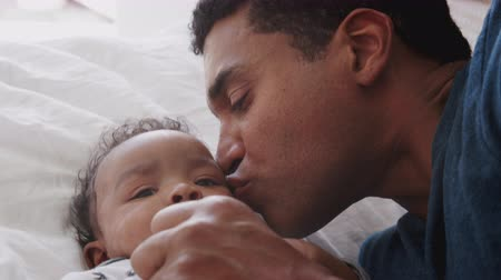 pocałunek : Close of millennial African American father lying on the bed kissing his baby son