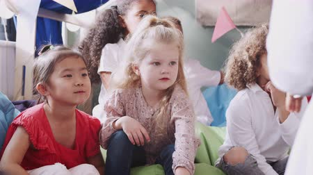 одноклассник : Infant school kids sitting on bean bags in a comfortable corner listening their teacher, close up