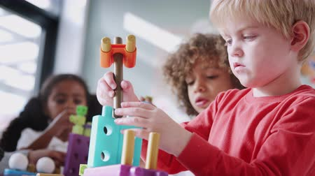 constructing : Infant school boy using educational construction toys with his classmates, low angle, close up