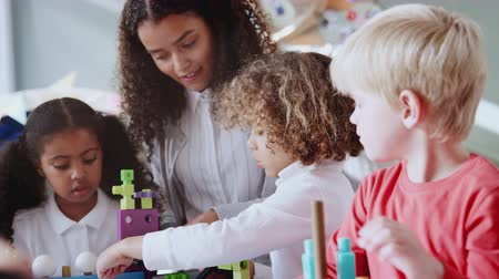 schoolkid : Female infant school teacher at table with three children using constructing blocks, selective focus Stock Footage