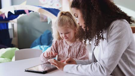 selektivní zaměření : Female infant school teacher working one on one with a young white schoolgirl using tablet, close up
