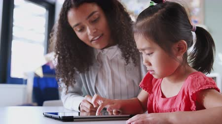 pré escolar : Female infant school teacher working with a young Asian schoolgirl using tablet, close up, low angle Stock Footage
