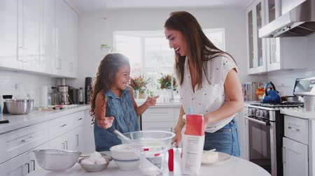 travessura : Mother and daughter preparing cake mix, tasting it and dabbing it on each other�s noses, close up