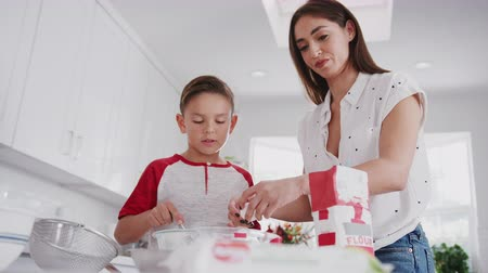looking down : Pre-teen Hispanic boy preparing cake mix in the kitchen with his mother, close up, low angle Stock Footage
