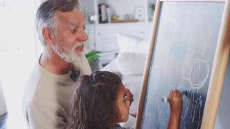 tablica : Senior man drawing on a blackboard with his young granddaughter at home