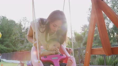 plac zabaw : Young Hispanic mother pushing her baby on a swing at a playground in the park, close up Wideo