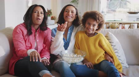 pré adolescente : Happy three generation female family group sit watching TV, laughing and eating popcorn together
