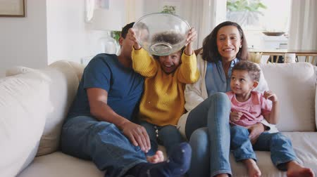 etnia africano : Young African American family sitting together watching a movie accidentally throwing popcorn in the air Stock Footage
