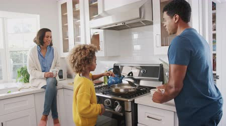 each other : African American parents and their pre-teen daughter preparing food together in the kitchen