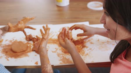 head over : Over shoulder view of two pre-teen girls playing with modelling clay at home, close up Stock Footage