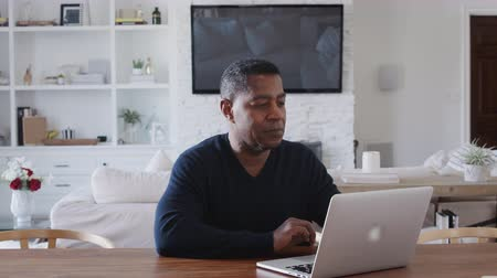 etnia africano : Middle aged African American man sitting at a table using laptop computer at home, close up, zoom in