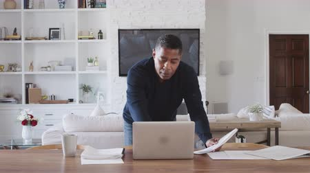 conveniente : Middle aged man standing at dining room table looking at paperwork and using laptop computer Stock Footage