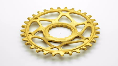 Golden oval bicycle chainring gear rotating at white background