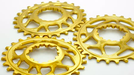 titanium : Golden oval bicycle chainring gear rotating at white background