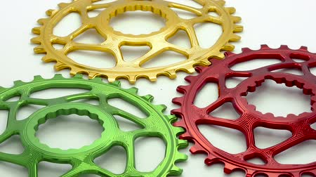 titanium : Colorful oval bicycle chainring gear rotating on a white background.