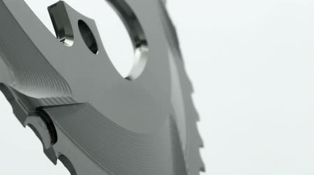 titanium : Black oval bicycle chainring gear rotating on a white background, strong close up with visible details of structure