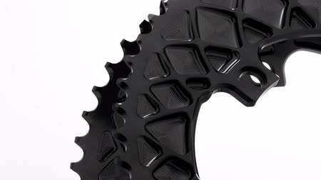 Black oval bicycle chainring gear rotating on a white background, strong close up with visible details of structure
