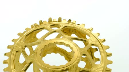 titanium : Golden oval bicycle chainring gear rotating on white background