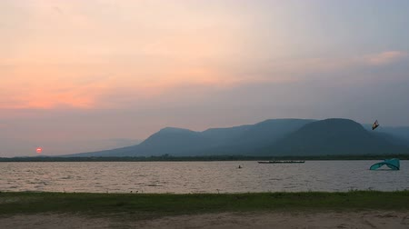 Kitesurfer swimming close to the sea coast. Beautiful orange sunset and Bokor mountain at the distance. Kampot, Cambodia.