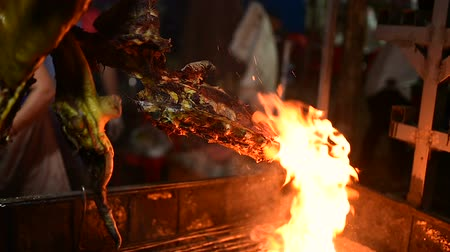 cambojano : Grilled pork on a spit, night market in Banlung town. Woman cutting a piece of meat that is hanging on the roast.