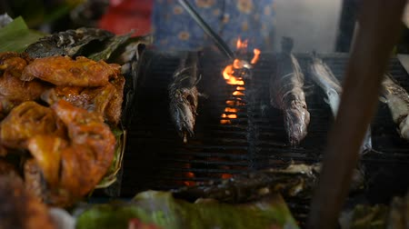 кхмерский : Grilled fish on the local food market in Banlung town. Red snapper and catfish are almost ready for lunch. Local seller turns the fish over to the other side.