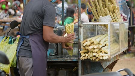 Cambodian man extracting sugar cane juice using machine on the street. In Cambodia, this super sweet juice is very popular. Sometimes they mix this juice with lemon to make better taste.