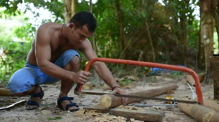 piŁa : Cambodian man prepares wood to build a traditional construction using handsaw. He incise wooden beam to fit with other wooden beam. 28 november 2017, Koh Rong Samloem. Cambodia.