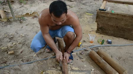 кхмерский : Cambodian man prepares wood to build a traditional construction using a tool like ax. He incise wooden beam to fit with other wooden beam. 28 november 2017, Koh Rong Samloem. Cambodia.