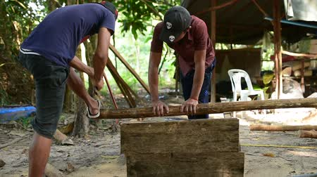 кхмерский : Cambodian man prepares wood to build a traditional construction using handsaw. He incise wooden beam to fit with other wooden beam. 28 november 2017, Koh Rong Samloem. Cambodia.