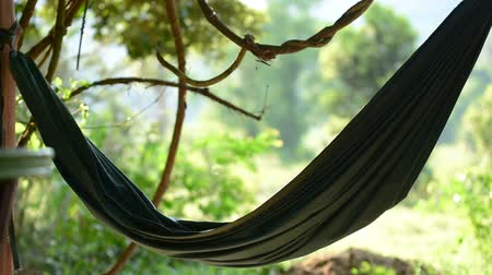 they : Green hammock flutters in the wind with the jungle in the background during daytime. Koh Rong Samloem island, Cambodia.