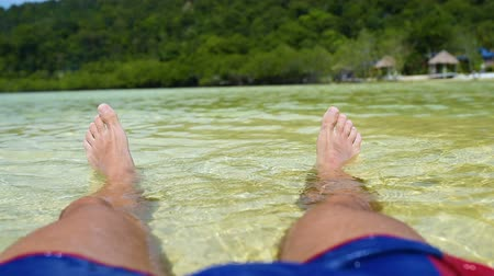 mentiras : Close-up of feet in ocean, man relaxing in blue water on summer beach vacation Vídeos