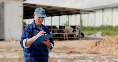 trabalhos domésticos : Farmer analyzing and writing on clipboard against cowshed Stock Footage