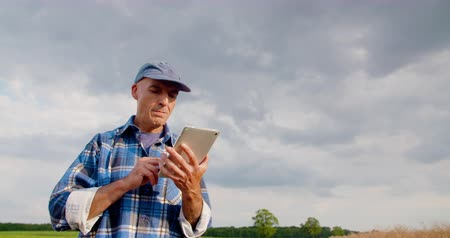 agronomist : Farmer using digital tablet at farm against blue sky and clouds. Stock Footage