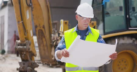 headwear : Confident mature male engineer analyzing blueprint Stock Footage