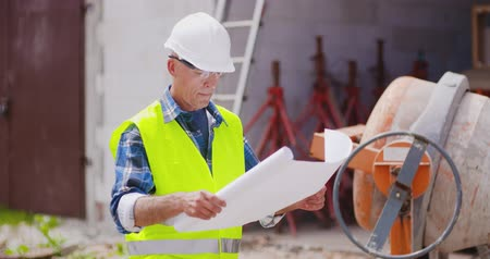 construction work : Confident mature male engineer analyzing blueprint Stock Footage