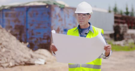 site : Confident mature male engineer analyzing blueprint Stock Footage