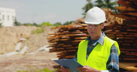 protective eyewear : Male worker examining planks stack