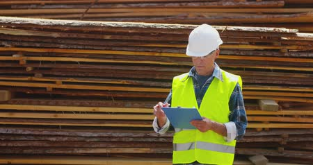 hardhat : Male worker examining planks stack