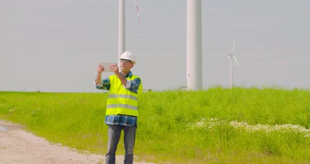 obnovitelný : Male engineer video conferencing against windmills