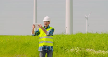 conferencing : Male engineer video conferencing against windmills