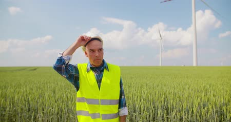 holding document : Engineer with blueprint analyzing farm against sky