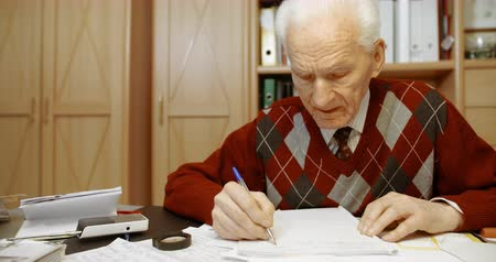 プルオーバー : Senior businessman writing on paper at table in office